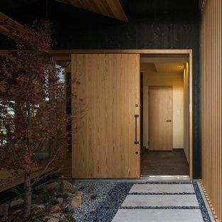 Bild på en mellanstor orientalisk ingång och ytterdörr, med beige väggar, mellanmörkt trägolv, en skjutdörr, ljus trädörr och beiget golv