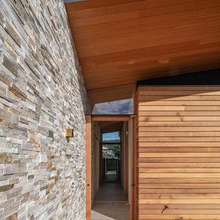 Стильный дизайн: узкая прихожая среднего размера в стиле модернизм с бежевыми стенами, мраморным полом, раздвижной входной дверью, входной дверью из дерева среднего тона и фиолетовым полом - последний тренд