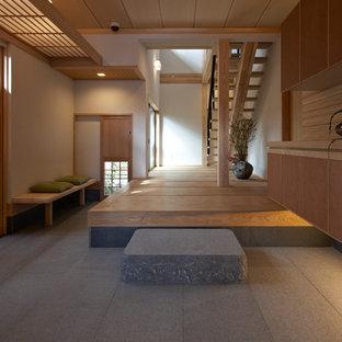 Réalisation d'un grand vestibule asiatique avec un mur blanc, une porte en bois clair et un sol gris.