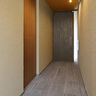 Modern inredning av en stor hall, med klinkergolv i keramik, en enkeldörr, mörk trädörr och grått golv