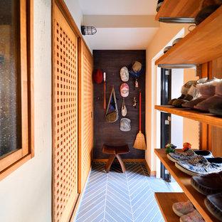 Imagen de entrada de estilo zen con paredes blancas, puerta corredera, puerta de madera en tonos medios y suelo negro