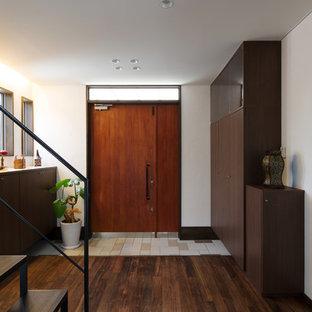 他の地域の片開きドアアジアンスタイルのおしゃれな玄関 (白い壁、濃色無垢フローリング、木目調のドア、茶色い床) の写真