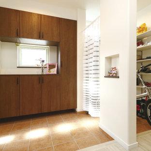 На фото: прихожие в современном стиле с белыми стенами, полом из терракотовой плитки, одностворчатой входной дверью, входной дверью из дерева среднего тона и коричневым полом