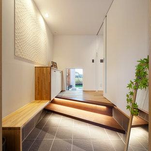 他の地域のアジアンスタイルのおしゃれな玄関ホール (白い壁、黒いドア、グレーの床) の写真
