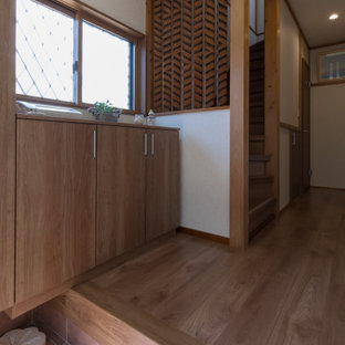 Modern inredning av en liten hall, med vita väggar, klinkergolv i terrakotta, en enkeldörr, mellanmörk trädörr och orange golv