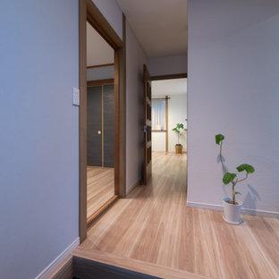 Ejemplo de hall papel pintado, nórdico, pequeño, con paredes azules, suelo de contrachapado, suelo beige y papel pintado