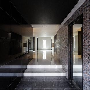 Modern inredning av en mycket stor hall, med svarta väggar, klinkergolv i porslin, en dubbeldörr, mörk trädörr och vitt golv