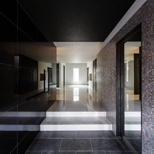 Imagen de hall papel pintado, moderno, extra grande, con paredes negras, suelo de baldosas de porcelana, puerta doble, puerta de madera oscura, suelo blanco y papel pintado