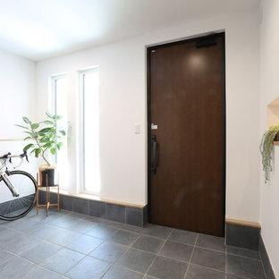 Cette photo montre une entrée moderne avec un couloir, un mur blanc, une porte simple, une porte marron et un sol vert.