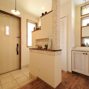 他の地域の片開きドアアジアンスタイルのおしゃれな玄関ホール (白い壁、淡色木目調のドア、ベージュの床) の写真
