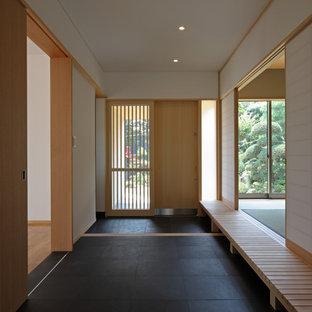 他の地域の広い引き戸アジアンスタイルのおしゃれな玄関ロビー (白い壁、淡色木目調のドア、黒い床) の写真