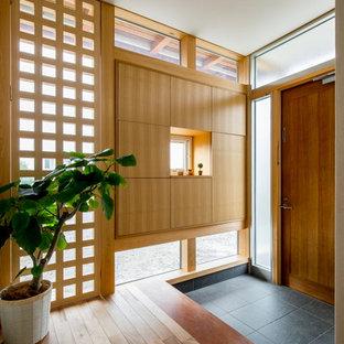 他の地域の片開きドアアジアンスタイルのおしゃれな玄関 (木目調のドア、グレーの床) の写真