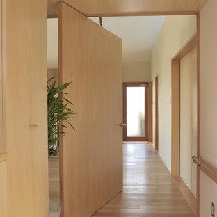 Aménagement d'une petit porte d'entrée asiatique avec un mur blanc, un sol en contreplaqué, une porte pivot, une porte marron et un sol marron.