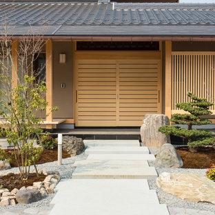 他の地域の引き戸アジアンスタイルのおしゃれな玄関ドア (茶色い壁、淡色木目調のドア) の写真