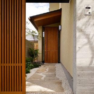 名古屋の引き戸アジアンスタイルのおしゃれな玄関ドア (ベージュの壁、木目調のドア、ベージュの床) の写真