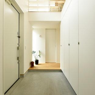 他の地域の片開きドアモダンスタイルのおしゃれな玄関ホール (白い壁、コンクリートの床、白いドア、グレーの床) の写真