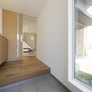 Идея дизайна: узкая прихожая в стиле модернизм с белыми стенами, полом из фанеры, одностворчатой входной дверью, черной входной дверью, коричневым полом, потолком с обоями и обоями на стенах
