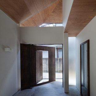 Inspiration för en liten funkis hall, med vita väggar, betonggolv, en enkeldörr, mörk trädörr och grått golv