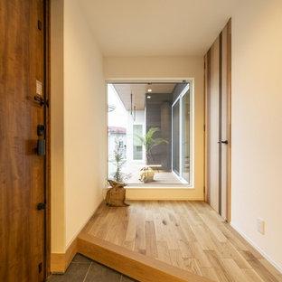 他の地域の中くらいの片開きドアモダンスタイルのおしゃれな玄関ホール (白い壁、淡色無垢フローリング、淡色木目調のドア、ベージュの床) の写真