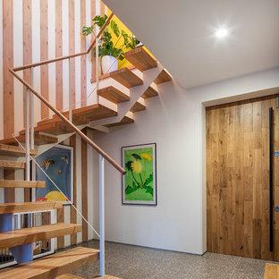 他の地域の片開きドアコンテンポラリースタイルのおしゃれな玄関 (白い壁、木目調のドア、グレーの床) の写真