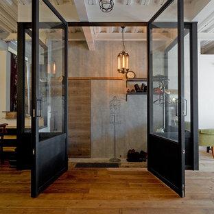 Идея дизайна: узкая прихожая среднего размера в стиле лофт с серыми стенами, бетонным полом, раздвижной входной дверью, входной дверью из дерева среднего тона и серым полом