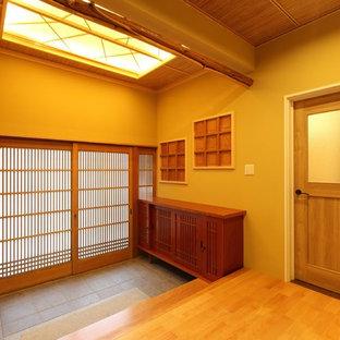 他の地域の引き戸和風のおしゃれな玄関ホール (茶色い壁、木目調のドア) の写真