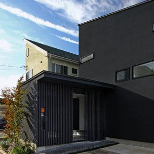 Réalisation d'une entrée asiatique de taille moyenne avec un mur noir, une porte coulissante et une porte en verre.