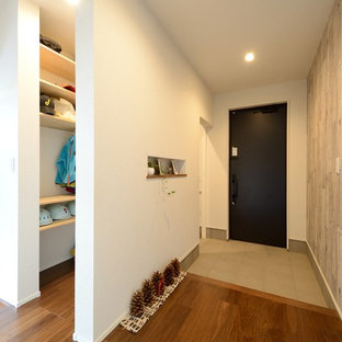 他の地域の片開きドアラスティックスタイルのおしゃれな玄関ホール (マルチカラーの壁、無垢フローリング、黒いドア、茶色い床) の写真