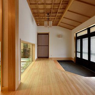 他の地域の広い引き戸アジアンスタイルのおしゃれな玄関ホール (白い壁、淡色無垢フローリング、黒いドア、茶色い床) の写真