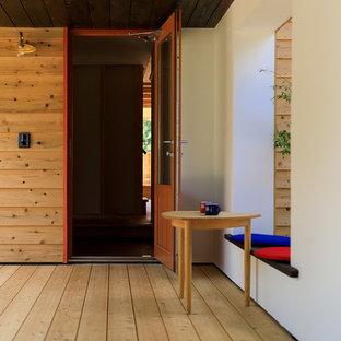 他の地域の片開きドアコンテンポラリースタイルのおしゃれな玄関ドア (白い壁、無垢フローリング、木目調のドア、茶色い床) の写真