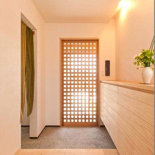 他の地域の片開きドアアジアンスタイルのおしゃれな玄関 (白い壁、グレーの床) の写真
