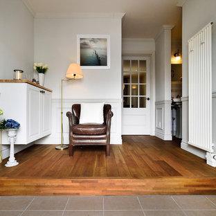 他の地域のトランジショナルスタイルのおしゃれな玄関ホール (白い壁、無垢フローリング、茶色い床) の写真