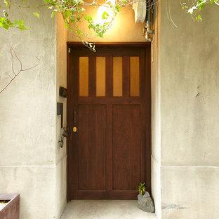 Exempel på en asiatisk entré, med grå väggar, betonggolv, en enkeldörr och mellanmörk trädörr