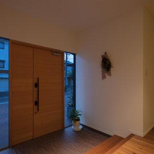 Aménagement d'un grand hall d'entrée moderne avec un mur blanc, un sol en contreplaqué, une porte double, une porte en bois brun et un sol marron.