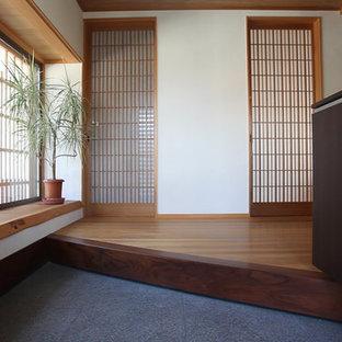他の地域の中くらいの引き戸アジアンスタイルのおしゃれな玄関ホール (白い壁、無垢フローリング、木目調のドア) の写真