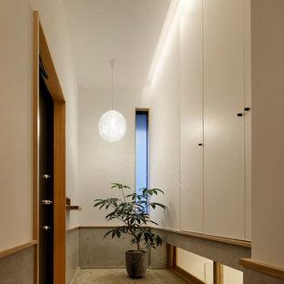 東京23区の小さい片開きドア北欧スタイルのおしゃれな玄関ホール (白い壁、黒いドア、ベージュの床) の写真