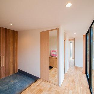 他の地域の中くらいの両開きドアコンテンポラリースタイルのおしゃれな玄関ホール (白い壁、木目調のドア、黒い床) の写真