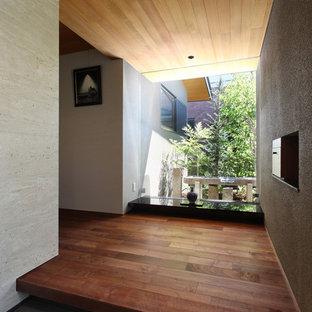 神戸の片開きドアモダンスタイルのおしゃれな玄関 (ベージュの壁、茶色いドア、グレーの床) の写真