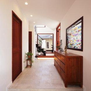 Exemple d'une entrée tendance avec un mur blanc et un sol noir.