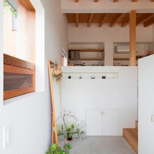 На фото: маленькая узкая прихожая в скандинавском стиле с белыми стенами, бетонным полом, раздвижной входной дверью, входной дверью из дерева среднего тона, серым полом и балками на потолке