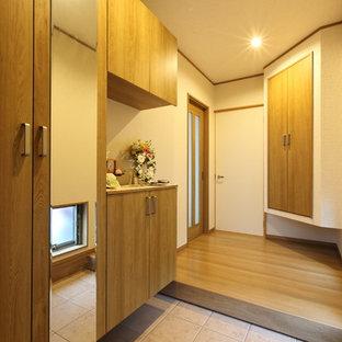 Asiatisk inredning av en mellanstor hall, med vita väggar, plywoodgolv, mellanmörk trädörr och brunt golv