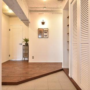 他の地域のインダストリアルスタイルのおしゃれな玄関 (白い壁、ベージュの床) の写真