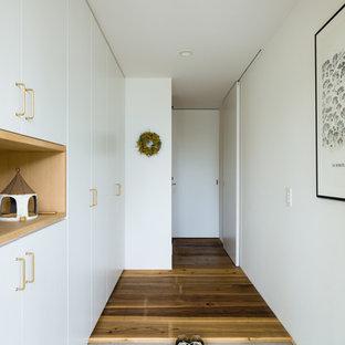 他の地域のモダンスタイルのおしゃれな玄関ホール (白い壁、コンクリートの床、グレーの床) の写真