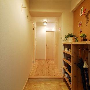 Выдающиеся фото от архитекторов и дизайнеров интерьера: маленькая узкая прихожая в современном стиле с белыми стенами, полом из винила, одностворчатой входной дверью, белой входной дверью и бежевым полом