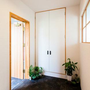 他の地域の中くらいの片開きドア和風のおしゃれな玄関ホール (白い壁、レンガの床、木目調のドア、黒い床) の写真