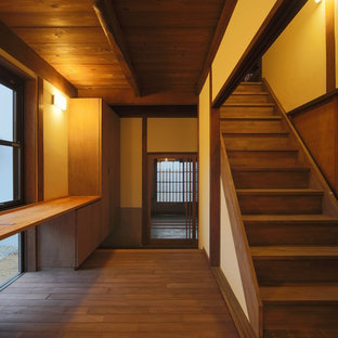 Inspiration for a large asian medium tone wood floor and brown floor entryway remodel in Other with white walls and a medium wood front door