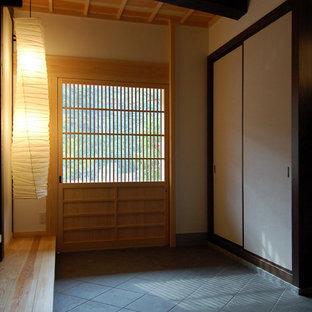Asiatischer Eingang mit weißer Wandfarbe, Porzellan-Bodenfliesen, Schiebetür, heller Holztür und grauem Boden in Sonstige