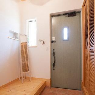 他の地域の片開きドアアジアンスタイルのおしゃれな玄関 (白い壁、テラコッタタイルの床、緑のドア、茶色い床) の写真