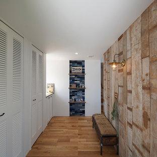 他の地域のビーチスタイルのおしゃれな玄関 (茶色い壁、グレーの床) の写真