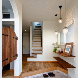 他の地域の片開きドア北欧スタイルのおしゃれな玄関 (白い壁、グレーの床) の写真